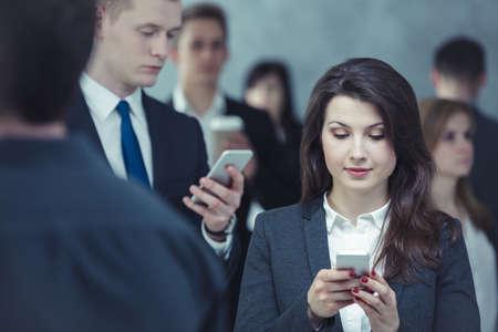 personas hablando: La gente está en constante control de sus teléfonos móviles Foto de archivo