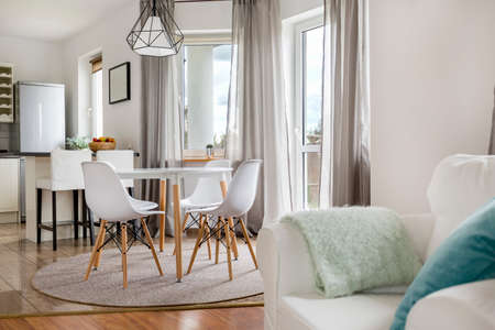 新しいラウンド テーブル、白い椅子とオープン キッチン フラット