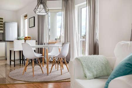 Appartement neuf avec table ronde, chaises blanches et cuisine ouverte