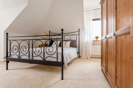 bed frame: Light bedroom with wooden wardrobe and bed with decorative metal frame Stock Photo