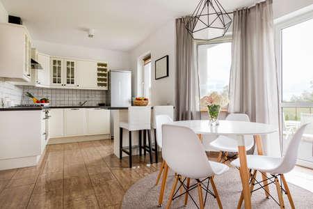 ラウンド テーブル、白い椅子、機能的なオープン キッチンが明るいスタイリッシュなインテリア
