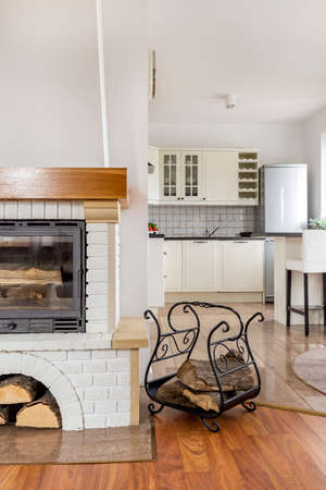 fireplace home: Light home interior with stylish fireplace and open kitchen Stock Photo