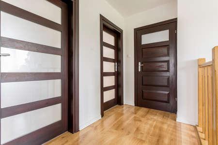 Couloir léger avec portes en bois et plancher brun