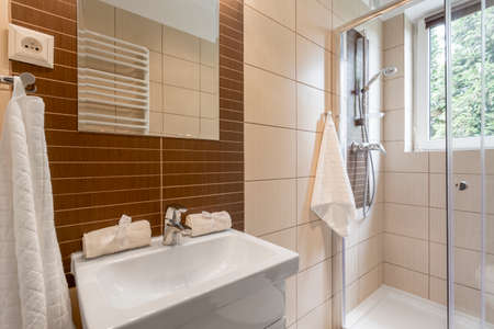 tiny: Small bathroom with brown tiling, mirror, shower and basin Stock Photo