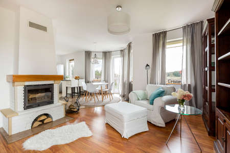 Cozy light flat interior with new furniture, fireplace and wooden floor panels