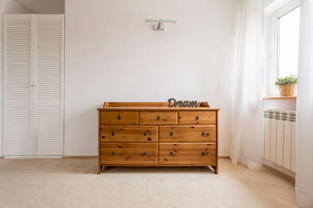Light bedroom with window and wooden dresser Stok Fotoğraf