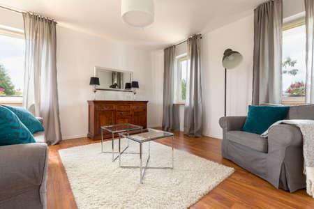 装飾的な窓のカーテン、ガラスのコーヒー テーブル、ソファ、アームチェア付きの居心地の良いリビング ルーム 写真素材