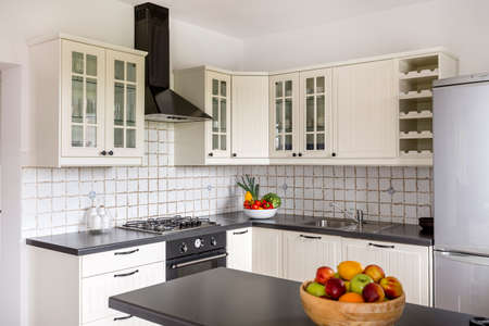 Stylish kitchen with white furniture, backsplash and solid worktop