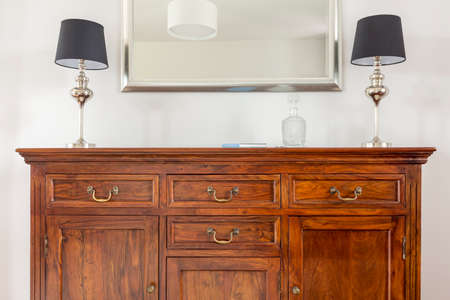 dresser: Stylish wooden dresser, two small lamps and mirror in a modern frame