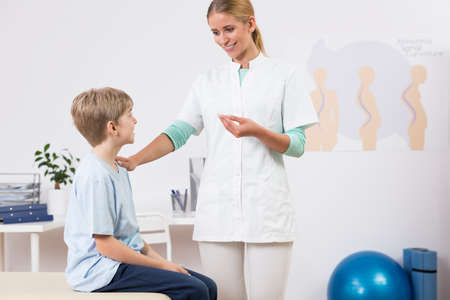 a medical examination: Shot of a young smiling doctor talking to a little boy in her office