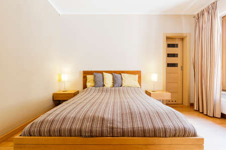 Shot of a king-size bed in a modern master bedroom