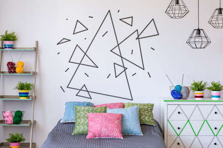 Shot of a white wall with triangles made with decorative tape Stock Photo