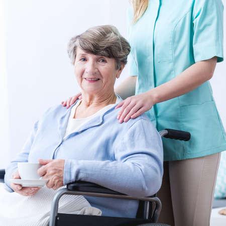 elderly woman: Image of senior woman drinking tea for indigestion Stock Photo