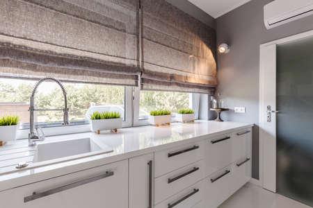 white kitchen: Shot of a modern grey kitchen with white furniture and big windows Stock Photo