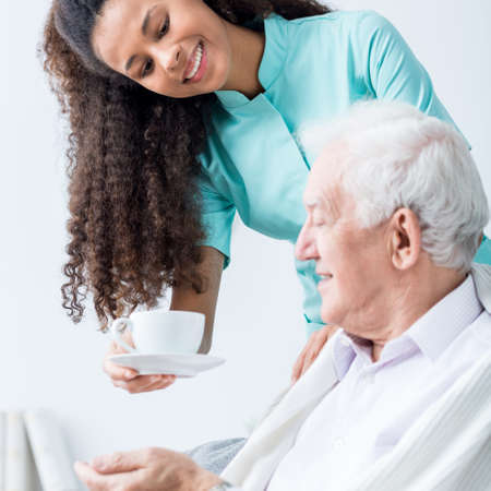 Caregiver giving senior man cup of coffee Stock Photo