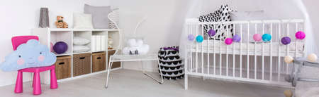 cot: Light baby room with white cot, chairs, white regale and stylish decorations, panorama