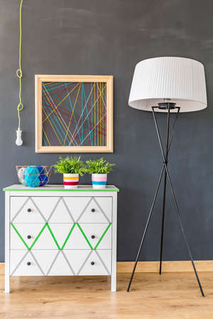 chest of drawers: Cropped shot of a white chest of drawers with decorated with washi tape, floor lamp and a crewel decoration on a black wall Stock Photo