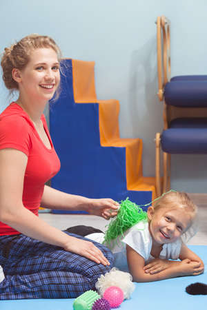 healthcare facility: Shot of a young therapist and her patient looking at a camera during a therapy