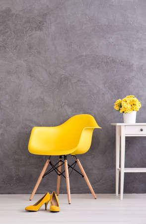 Gele minimalistische stoel op een cyaan muur achtergrond met de witte commode met bloempot zich dicht en gele hoge hakken op de vloer Stockfoto