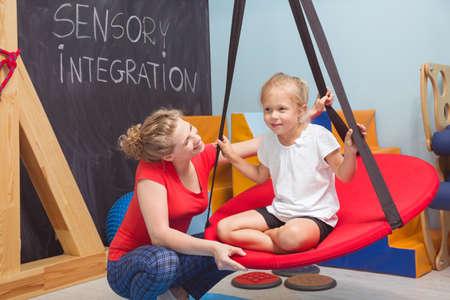Foto de una niña sonriente goza de una terapia sensorial en un columpio mientras que su fisioterapeuta ayudar a su Foto de archivo
