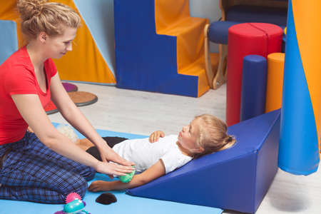 Shot of a little girl lying on the triangle pillow while therapist massaging her arm