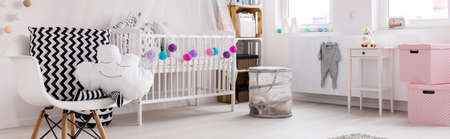 cot: Spacious, light child room with white cot, chairs and colorful decorations, panorama