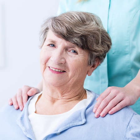 buoyancy: Smiling senior woman supported by caregiver or nurse