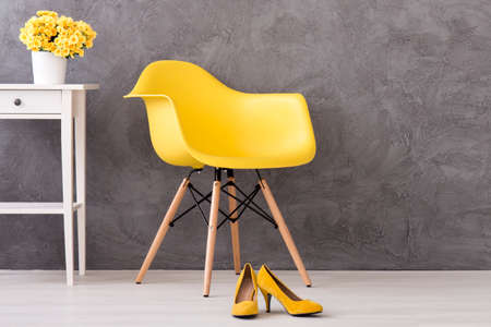 commode: Yellow minimalistic chair on a cyan wall background with the white commode standing close and yellow high heels on the floor Stock Photo