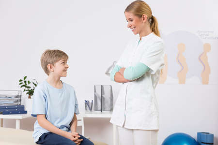 posture correction: Shot of a young doctor talking with a little boy in her office