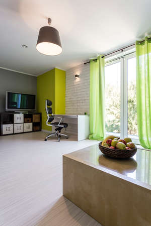 spacious: Shot of a spacious modern home office with green curtains