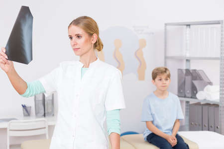 deformity: Shot of a doctor looking at an x-rey photo while a little boy is sitting on a bed in her office Stock Photo