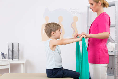 deformity: Shot of a young physiotherapist showing to his patient how to exercise with an exercise band Stock Photo