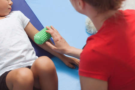 color therapist: Shot of a therapist using a roll massage on a little girls arm during a therapy