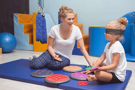 Disparo de un fisioterapeuta y sonriente con su pequeño paciente con los ojos cubiertos durante una terapia de la mano