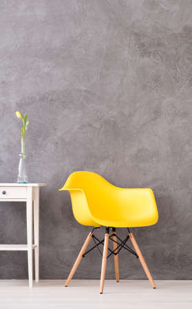 commode: Yellow minimalistic chair on a cyan wall background with the white commode close