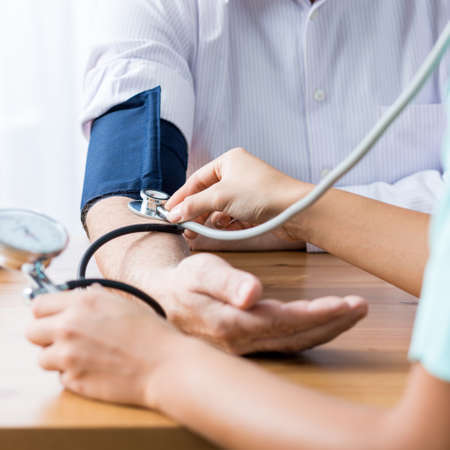 pressure: Close up of patient and doctor taking blood pressure Stock Photo