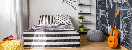 wall decoration: Room interior with poufs, bed, minimalistic rack and the guitar Stock Photo
