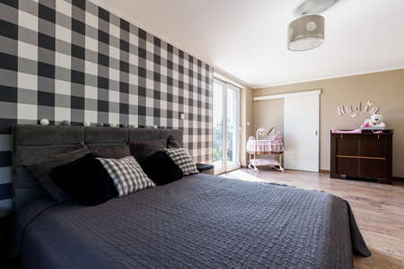 kingsize: Shot of a king-size bed and a crib in a modern bedroom