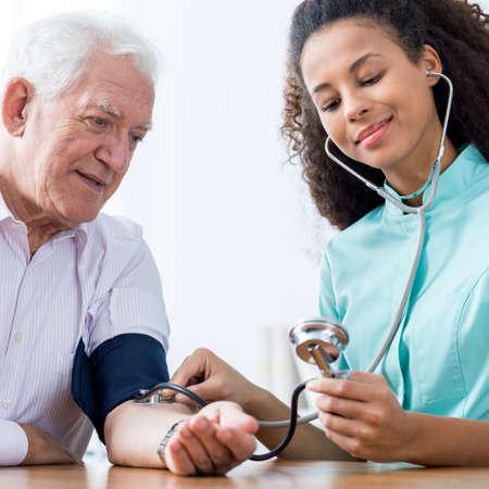 Photo of old male and nurse taking blood pressure Archivio Fotografico