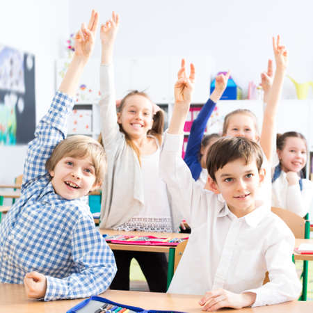 Shot of a group of students raising their hands in a classroom Stock Photo
