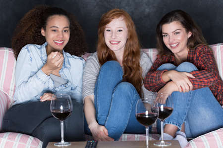 young women: Shot of three happy young women sitting on a sofa and watching a movie