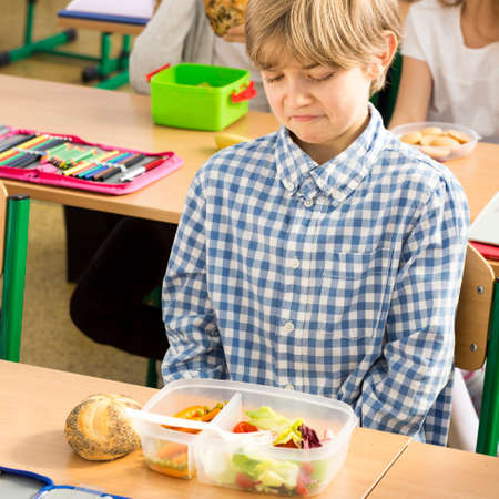 school boy: Shot of a little boy sitting in a classroom and looking at his lunch