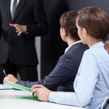 workmate: Businesswomen sitting at the desk during business conference Stock Photo