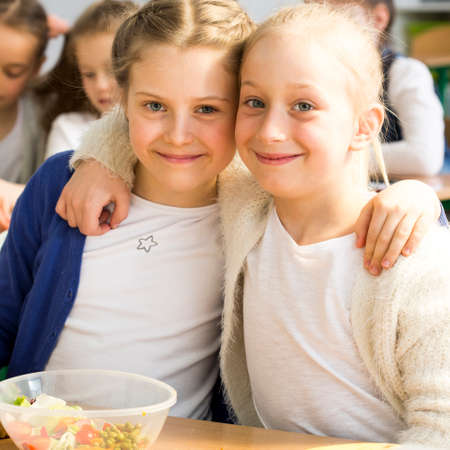 Shot of two girls hugging in a classroom