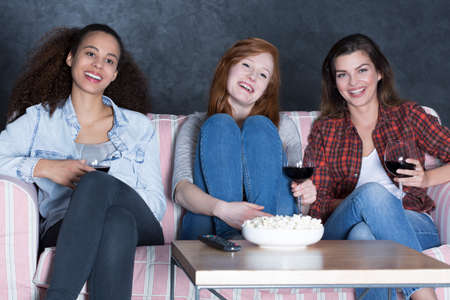 people laughing: Shot of three girlfriends laughing while watching a movie