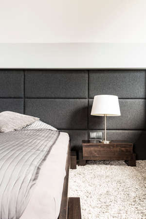bedside lamps: Shot of a bed and a wooden night table with a lamp in a modern bedroom