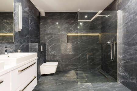 Colpo di un elegante bagno bianco e nero con una doccia in vetro