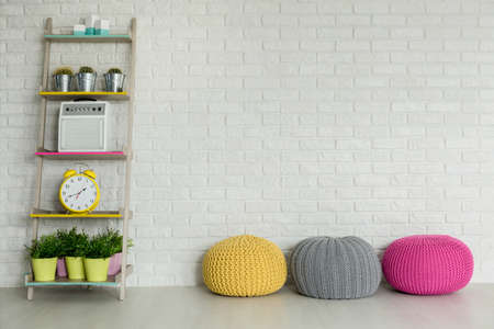 yellow fleece: Light interior with DIY regale, colorful poufs and brick wall