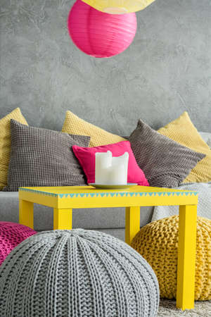 yellow fleece: New room in grey with sofa, yellow table and handmade wool pouf Stock Photo