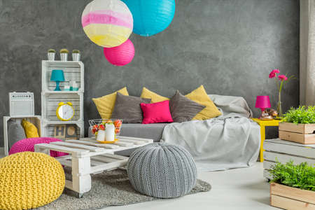 pouf: Grey living room with DIY furniture, sofa, wool poufs, colorful shades and green plants